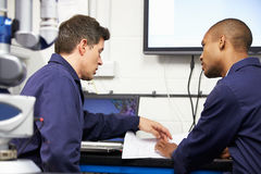 Two Engineers Discussing Plans With CMM Arm In Foreground Royalty Free Stock Image