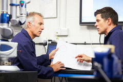 Two Engineers Discussing Plans With CMM Arm In Foreground Stock Images