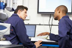 Two Engineers Discussing Plans With CMM Arm In Foreground. Sitting Down At Desk Stock Image