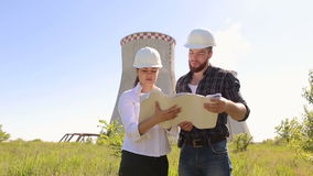 Two engineers with drawings on construction site. Two construction engineer man and woman in white protective helmets are working with the drawings on the stock video