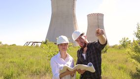 Two engineers in helmets with drawings in outdoors. Two construction engineer man and woman in white protective helmets are working with the drawings on the stock video footage