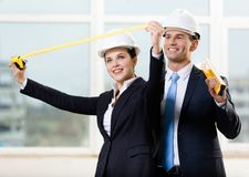 Two engineers keeping level and tape measure Royalty Free Stock Photos
