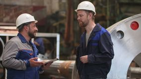 Two engineers with laptop communicate and smile in heavy industry factory.  stock footage