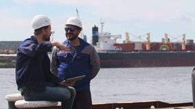 Two engineers with laptop smile and communicate in Shipping cargo port.  stock video footage
