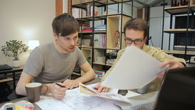 Two engineers are looking at the blueprints sitting at the table. stock footage