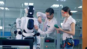 Two engineers are measuring technical parameters of a robot