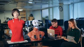 Two engineers are observing a robotic mannequin moving facial organs stock video footage