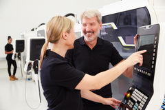 Two Engineers Operating CNC Machinery On Factory Floor Stock Photos