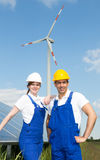 Two engineers posing with wind turbine and solar panels Royalty Free Stock Photos