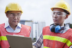 Two engineers in protective workwear looking down at a clipboard outside of a factory Stock Photos