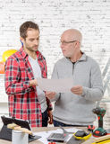 Two engineers reading a plan in office Stock Photography