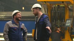 Two engineers smile, laugh and shake hands in heavy industry factory stock footage
