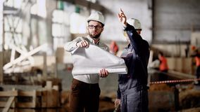 Two engineers standing in building site and holding construction plan. Men in white hardhats working discussing detailes