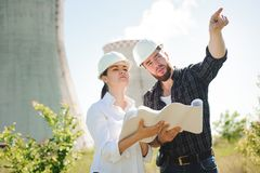 Two engineers standing at electricity station, discussing plan stock image