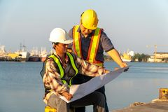 Free Two Engineers Stood Wearing A Safety Helmet. Standing At The Pier And Holding The Blueprint And Consult The Plan In The Constructi Royalty Free Stock Photo - 160117135