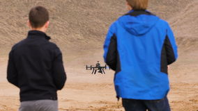 Two engineers watching the drone landing. Quadrocopters sits in automatic mode,. On gps coordinates stock video footage