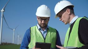 Two engineers discussing against wind turbines. Two engineers wearing hard hat discussing over digital table against turbines on wind farm stock video