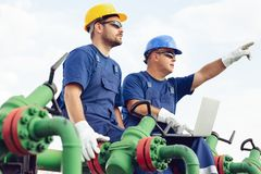 Two engineers working inside oil and gas refinery. Two young engineers working inside oil and gas refinery royalty free stock images