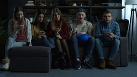 Group of young friends watching sport tv at home stock footage