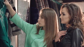 Two enjoyable ladies choosing the coats in boutique. In full HD stock footage