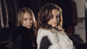 Two enjoyable ladies posing in rich fur coats in boutique. Slowly. Two enjoyable ladies posing in rich fur coats in boutique for advertising. Slowly stock video footage