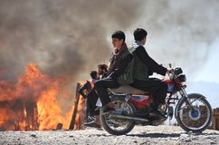 Two boys enjoying on motorcycle while woods stalls are burning. royalty free stock photos