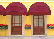 Two entrances with nostalgic red marquee, italy. Yellow facade with two entrances, nostalgic red marquee, italy Royalty Free Stock Photo