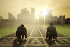 Two entrepreneurs ready to compete. Rear view of two worker wearing formal suit and kneeling on the start line to compete Royalty Free Stock Image