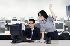 Two entrepreneurs show success expression. Portrait of two young entrepreneurs showing success expression by raising their hands in the office Stock Images