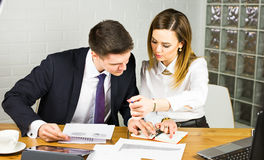 Two entrepreneurs sitting together working in an office desk comparing documents. Stock Photography