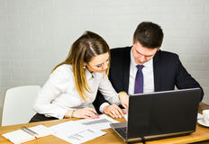 Two entrepreneurs sitting together working in an office desk comparing documents. Royalty Free Stock Photography