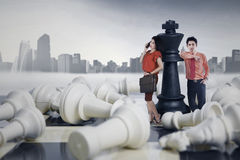 Two entrepreneurs standing on the chessboard Royalty Free Stock Images