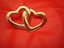 Two Entwined Hearts. On red background Stock Image