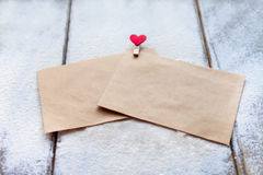 Two the envelope of the Kraft paper clip in the shape of a heart in snow on Valentine`s day, people`s attitudes Stock Photos