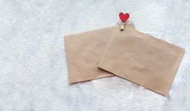 Two the envelope of the Kraft paper clip in the shape of a heart in snow on Valentine`s day, people`s attitudes Royalty Free Stock Photos