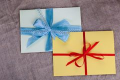 Two envelope sacking tied with ribbon. Two envelope sacking tied with blue and red ribbon Royalty Free Stock Image