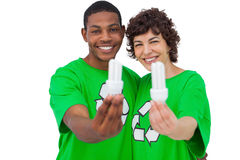 Two environmental activists holding energy saving light bulbs Stock Photos