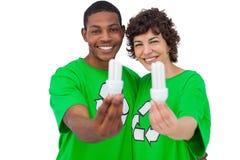 Two environmental activists holding energy saving light bulbs. On white background Stock Photos