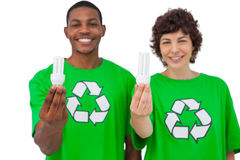 Two environmental activists holding light bulbs Royalty Free Stock Images
