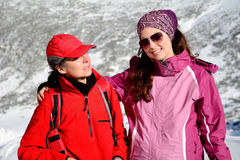 Two equipped hiker women hugging  in a high winter mountain.Mother and daughter Stock Images