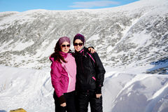 Two equipped hiker women hugging  in a high winter mountain.Sisters Stock Images