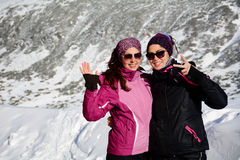 Two equipped hiker women hugging  in a high winter mountain.Sisters. Beautiful Hiker women hugging and smiling in  a winter mountain Stock Images