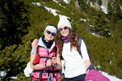 Two equipped hiker women laughing  in a high mountain Royalty Free Stock Images