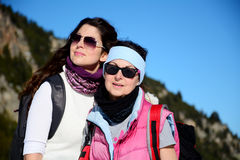 Two equipped hiker women laughing  in a high mountain Stock Photos