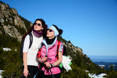 Two equipped hiker women laughing  in a high mountain Royalty Free Stock Image