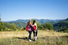 Two Equipped women hiking in a high autumn  mountain Royalty Free Stock Photography