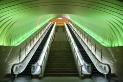 Two Escalators with Green Light overhead Royalty Free Stock Image