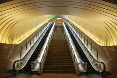 Two Escalators with Yellow Light overhead Stock Photography