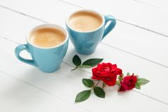 Two espresso coffee cups and red rose flowers on white background. Royalty Free Stock Images