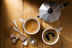 Two espresso and a coffee maker on a rough wooden table Stock Images